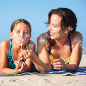 mother and daughter blowing bubbles on the beach